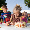 Siblings Molly, 8, center, Austin, 6, left, and Abby Fulkerson, 4, all of New Albany, work on drawings at the Floyd Action Network booth during the S. Ellen Jones Neighborhood Festival in New Albany on Saturday morning. The drawings by the Fulkersons and other kids at the event will be displayed at the old Emery's Ice Cream Building once it has been fully restored. Staff photo by Christopher Fryer