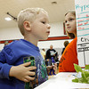 Holden Graf, 4, of Georgetown, left, looks over Slate Run Elementary School student Destiny Hardy's science experiment on pumpkin seed growth during the Elementary Science Exhibit at Nathaniel Scribner Middle School in New Albany on Monday evening. The grade level winners from all nine New Albany-Floyd County elementary schools were recognized for their achievements at the exhibit. Staff photo by Christopher Fryer