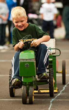 Griffin Lorfing, 6, of Greenville, strains to pull as far as possible during the children's tractor pull next to the Harvest Homecoming Stage along State Street in downtown New Albany on Saturday morning. Staff photo by Christopher Fryer