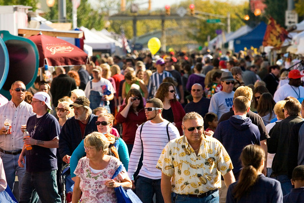 Craft and food booths line Pearl Street as people make their way through the area during Harvest Homecoming festivities on Thursday afternoon in downtown New Albany. Staff photo by Christopher Fryer