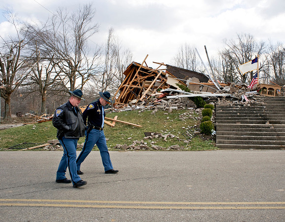 Indiana State Troopers 1st Sgt. Jamey Noel, left, and Lt. Col.  Phillip Parker walk past what remains of the Mt. Moriah church on Henryville Otisco Rd. Sunday afternoon. An EF-4 tornado hit the area last Friday afternoon killing 10 people in Southern Indiana and Northern Kentucky. Staff photo by Christopher Fryer