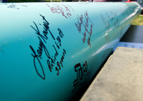 Signatures from Duke Energy employees line the outside of a new time capsule that was placed in the ground after the capsule from 1987 was removed and opened during a ceremony at the company's Clarksville location on Wednesday morning. This year also marks the company's 100th anniversary. Staff photo by Christopher Fryer