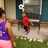 Amon Armour, 7, plays soccer with his cousin, Heavynn Douglas, 9, both of Jeffersonville, in front of his family's home on Thursday afternoon during a send off party to wish him well at this year's World Dwarf Games at Michigan State University. Armour was born with achondroplasia, which is a form of dwarfism. He will compete at the games in football, track and field, basketball, floor hockey, and soccer. Staff photo by Christopher Fryer