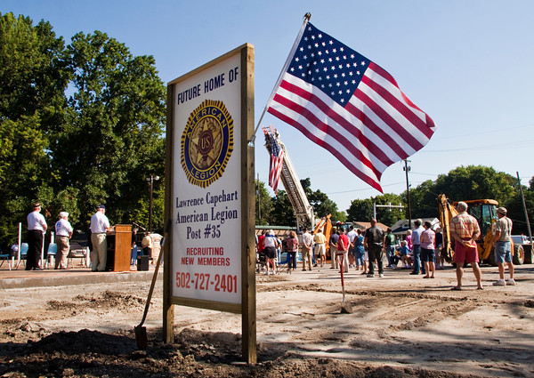 Attendants face the American Flag while retired Navy veteran Jim Gilbert, of Jeffersonville, speaks about its history during the ground-breaking ceremony for the new American Legion Post 35 building in Jeffersonville on Saturday morning. Staff photo by Christopher Fryer