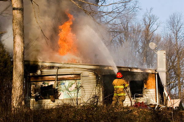 A New Chapel firefighter battles flames at the residence of Billy Fulkerson, 2058 Two Mile Lane, on Wednesday afternoon in Floyd County. No injuries occurred during the fire. Staff photo by Christopher Fryer