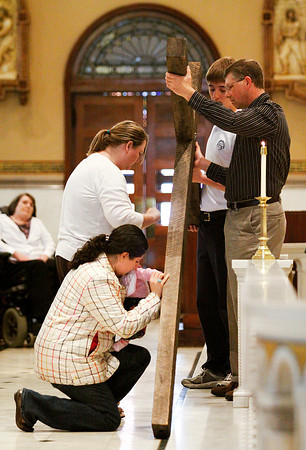 Jennifer Vizhnay, of Sellersburg, holds her daughter Zaina, four months, as she kneels down during the veneration of the cross at the Good Friday service at St. Mary's Catholic Church on Friday afternoon in downtown New Albany. Staff photo by Christopher Fryer
