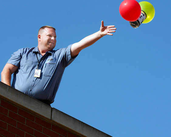 Willie Liter, lead custodian at Highland Hills Middle School in Floyds Knobs, tosses a student's egg drop project from the top of the school. Fifth-graders built devices to protect eggs from falls in their science classes. Staff photo by Jerod Clapp
