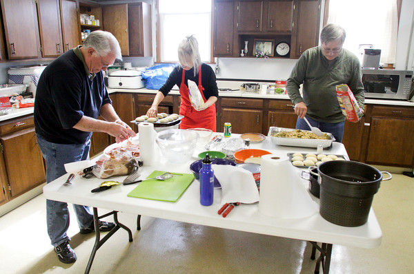 From left, volunteers Brett Wilson, Deborah Henderson and Steve Voelker, all of Jeffersonville, prepare food to be served during a Thanksgiving dinner for victims of the March 2 tornadoes in the basement of St. Francis Xavier Catholic Church in Henryville on Thursday afternoon. Staff photo by Christopher Fryer