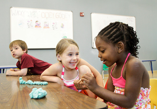 Julianne Traub, 5, left, and Jayla Gunn, 5, goof around with edible play dough during craft time at the New Albany YMCA's Wacky Tacky Ooey Gooey themed Kinder Camp on Thursday afternoon. Staff photo by Christopher Fryer