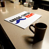 A campaign sign for Democratic gubernatorial candidate John Gregg sits next to a coffee mug on the bar at the Hitching Post Tavern during a stop on his statewide bus tour in downtown New Albany on Friday morning. Friday was the seventh day of his eight day bus tour through 72 Indiana cities that ends today in Indianapolis. Staff photo by Christopher Fryer
