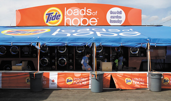 Tide's Loads of Hope staff sort laundry Wednesday afternoon in Henryville as part of the tornado relief effort. Residents can drop off two loads of laundry per day and program staff will wash, dry and fold it. Staff photo by Christopher Fryer