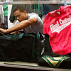 Senior Brantley Seawright places a sports bag inside a display case in Highlander Outfitters at Floyd Central High School on Friday morning. The store sells Floyd Central apparel and accessories and is run by 35 students as part of a business management class. Staff photo by Christopher Fryer