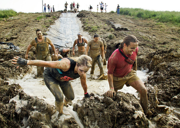 Who's Your Mudder? team members Andrea Thomas, left, of Charlestown, and Brent Evans, of Louisville, make their way through an obstacle during the Muddy Fanatic 5K Adventure Race at the former Glenwood Training Center in Sellersburg on Saturday morning. Over 2000 participants negotiated over 30 obstacles on a 3.1 mile course either as individual racers or as part of a team. Staff photo by Christopher Fryer
