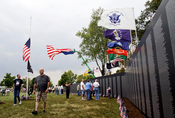 Flags wave overhead as people visit the American Veterans Traveling Tribute Vietnam Wall next to the Clarksville Municipal Center along Veterans Parkway on Friday afternoon. Staff photo by Christopher Fryer