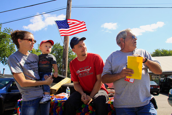 From left, Zandria Hall, Rayce Basham, 13 months, Jason Basham, all of Henryville, and Freddie Hall, of Underwood, look on during the Henryville Community Day Parade on Saturday morning. Staff photo by Christopher Fryer