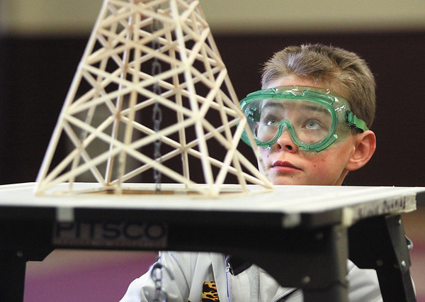 Highland Hills Middle School seventh-grader Ethan Worrall keeps a close eye on his team's balsa wood tower as he adds weight to it Saturday morning during the 2012 Science Olympiad at Indiana University Southeast.  Staff photo by C.E. Branham