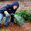 Michael Kendall, a second-grader from Fairmont Elementary, waters some plants along the side of Hazelwood Middle School for Hazelwood Gives a Day on Saturday. Kendall was helping his brother and sister, Thomas and Heather, who both attend Hazelwood. Staff photo by Jerod Clapp