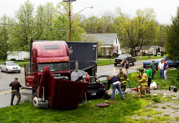 Emergency officials, with the Georgetown Township Fire Department and the Floyd County Sheriff's Department, work the scene of a two-vehicle, injury accident involving a semitrailer and a passenger vehicle at the intersection of Greenville Georgetown Road and Ind. 64 in Georgetown on Wednesday afternoon. The accident occurred at about 3:45 p.m. and the 17-year-old male driving the passenger vehicle was transported to University of Louisville Hospital after being extricated from the vehicle. Staff photo by Christopher Fryer