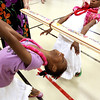 Third-graders Lajoy Williams, left, and Ligia Williams enjoy going under the limbo bar at Wilson Elementary School's Literacy Luau Tuesday evening. The family night event provided dinner, grade level reading activities and limbo. Staff photo by C.E. Branham