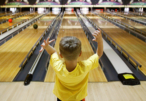 Tyler Sharp, 5, of Floyds Knobs, celebrates as his ball strikes the pins at Hoosier Lanes Strike and Spare in New Albany on Thursday morning. Five daycare centers from Floyd and Clark counties brought 138 children out to encourage networking between the centers and celebrate Week of the Young Child. Staff photo by Christopher Fryer