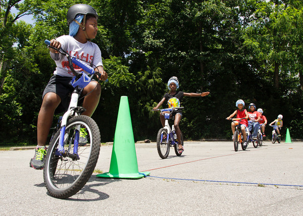 Participants work on turn signals while looping around part of the bicycle safety rodeo course at the Griffin Center on Friday afternoon in New Albany. About 20 participants from the Riverside, Parkview and Griffin Street recreation centers learned about traffic rules and general bicycle safety in the Kosair Children's Hospital event through the New Albany Department of Parks and Recreation. Staff photo by Christopher Fryer