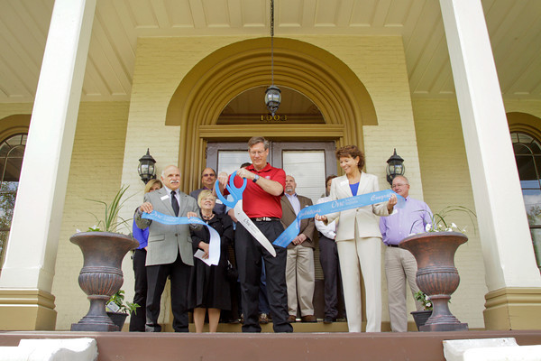 Owner Ron Smith cuts a ribbon during the official grand opening of the Pepin Mansion, located at 1003 E. Main St., in New Albany on Thursday afternoon. Smith is operating the newly restored, historic home as a retreat center, rehearsal hall and bed and breakfast. Staff photo by Christopher Fryer