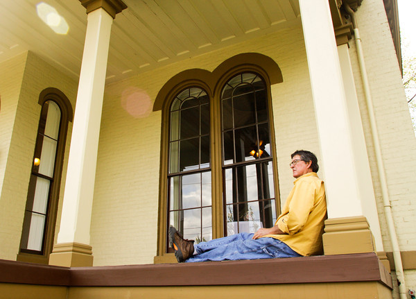 R. Michael Wimmer, of New Albany, sits on the front porch of the Pepin Mansion, located at 1003 E. Main St., in New Albany on Thursday afternoon. Owner Ron Smith held an official grand opening for the restored home on Thursday, which he is operating as a retreat center, rehearsal hall and bed and breakfast. Staff photo by Christopher Fryer