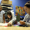 Alaya Bolds, 7, and Heaven Blalock, 10, work with attendance clerk Ashley Cohron on All About Me Books at the Ed Endres Boys & Girls Club at its open house on Tuesday. The club opened its doors to community members and donors to show them what it does for the community. Staff photo by Jerod Clapp