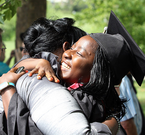 Niza Phiri receives a hug from friend Marleesha Cooper before commencement ceremonies Monday afternoon at Indiana University Southeast. Staff photo by C.E. Branham