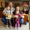 Michael and Cassie Norman hold their daughters, Liberty, left, and Annabelle, in their New Washington home on Friday afternoon. Staff photo by Christopher Fryer