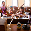 From left, Kaydence, 5, and Aleigha Ashby, 3, and their cousin Derreon Austin, 2, all of New Albany, play with slate tablets in the fourth-grade classroom of the historic Division Street School during the fourth-annual Ice Cream Social in New Albany on Saturday afternoon. The event is put on by the Friends of the Division Street School to celebrate the continuation of their project as well as to get the public into the historic building to help educate them on a part of New Albany's history. Staff photo by Christopher Fryer