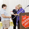 Cheryl McCrumb, left, receives a gift from Corps Officer Stephen Kiger, center, and Business Administrator Roxanne Haley while being recognized for her service at the Salvation Army Volunteer Luncheon in New Albany on Wednesday afternoon. McCrumb is a retired chef, and helped to organize the food preparation and distribution to area relief centers when the March 2 tornadoes hit last year. Staff photo by Christopher Fryer