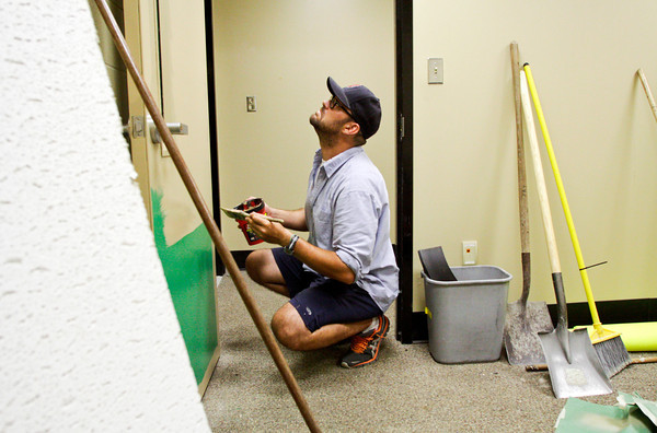 Floyd County employee Michael Zacharski, of Louisville, paints a door in the old Pine View Elementary School on Thursday afternoon in New Albany. The former school has been re-shaped to house a new youth shelter and various other county offices. Staff photo by Christopher Fryer