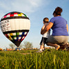 Stacy Cox and her son Mason Emery, both of New Albany, look on as balloon pilot Jerry Copas and his chase crew inflate a hot air balloon in Clarksville before a flight across part of southern Indiana on Monday evening. Copas will be competing in the Kentucky Derby Festival Great Balloon Race this week. Staff photo by Christopher Fryer