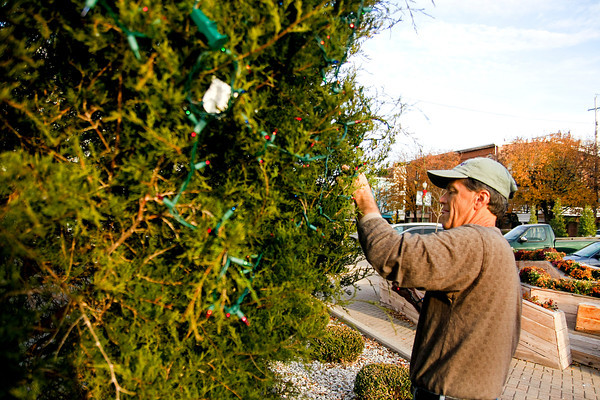 David Barksdale, Develop New Albany volunteer and Floyd County historian, strings up lights on the New Albany city holiday tree on Monday to prepare for Holiday Fest. The city's annual holiday celebration is on Saturday from 1 p.m. to 6:30 p.m. Staff photo by Jerod Clapp