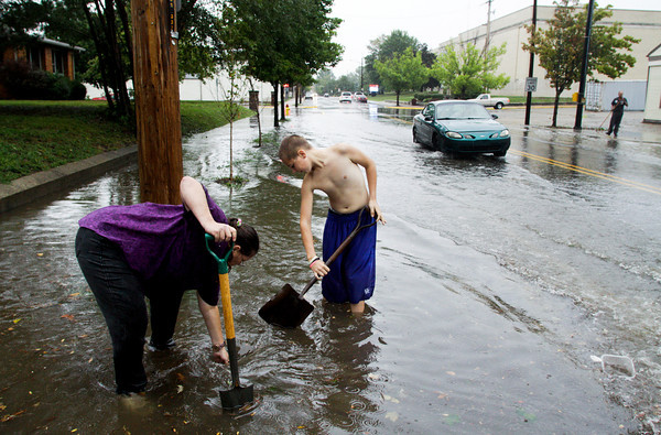 Mary Stringer, left, and Justin Good work to clear a storm drain along the 800 block of Vincennes Street in New Albany after a thunderstorm moved through the area on Wednesday afternoon. They said that every time there is a heavy rain they have to clear debris to prevent basement flooding in their rental property. Staff photo by Christopher Fryer