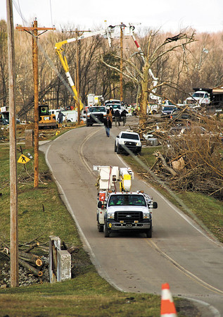 Utility crews work to repair powerlines on Henryville Otisco Rd. Sunday afternoon. Staff photo by Christopher Fryer
