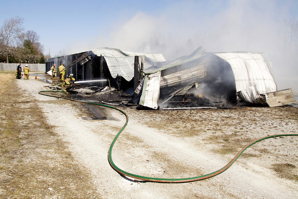 Firefighters work to contain a blaze at D&D Mini Storage, located along the 13000 block of U.S. 31, in Memphis on Tuesday afternoon. There was smoke damage to the entire 34 unit structure, and fire damage to 80 percent of the building. Staff photo by Christopher Fryer