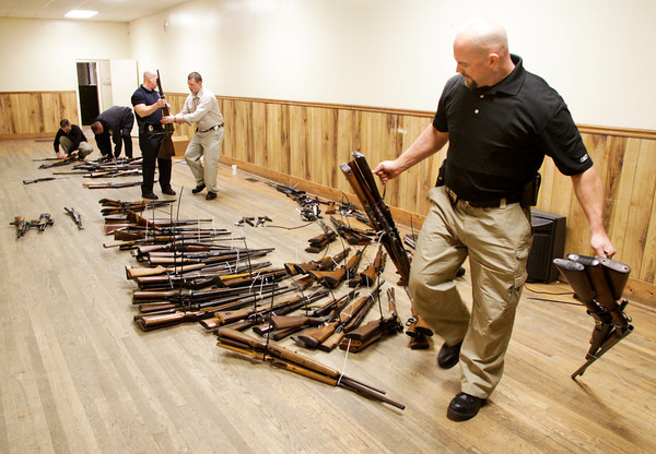 New Albany police officers organize firearms after they were purchased during a buyback program at the Ekin Avenue Recreation Center in New Albany on Friday afternoon. The buyback lasted less than two hours and 249 firearms were purchased before the $50,000 ceiling for the program was reached. Staff photo by Christopher Fryer