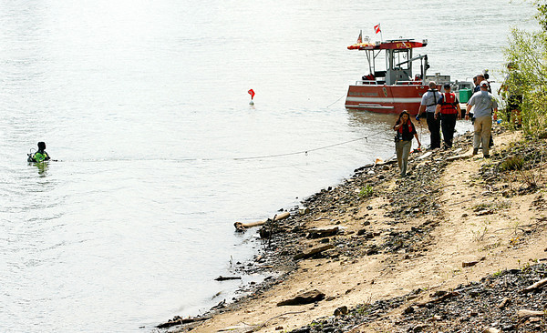 Officers and divers from various agencies search the Ohio River and the Indiana riverbank near the Sherman Minton Bridge on Thursday afternoon. Staff photo by Christopher Fryer