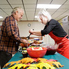 Volunteer Deborah Henderson, of Jeffersonville, serves John Watson, of Henryville, during a Thanksgiving dinner for victims of the March 2 tornadoes in the basement of St. Francis Xavier Catholic Church in Henryville on Thursday afternoon. Staff photo by Christopher Fryer