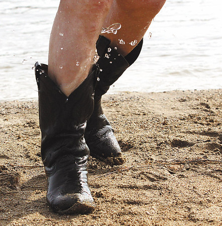Water shoots out of the cowboy boot of a Polar Plunge participant.  Staff photo by C.E. Branham