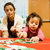 Julia Dwyer helps her daughter Layla, 2, construct a wreath at a craft station during Santa's Weekend Workshop at the Griffin Center in New Albany on Saturday morning. Staff photo by Christopher Fryer