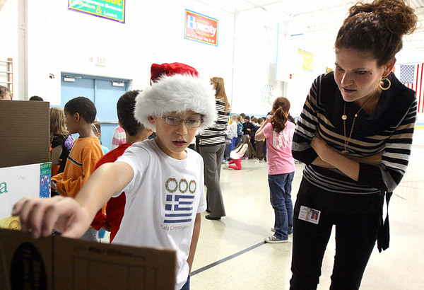 Thomas Jefferson Elementary School third-graders studied Christmas traditions around the world and displayed their research Wednesday at the school. Student Cruz Andres, above, explains Greek Christmas traditions to second grade teacher Andrea Thomas. Staff photo by C.E. Branham