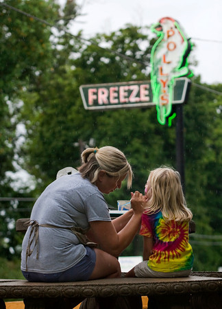 Kari James, of Charlestown, paints an ice cream cone on Taylor Young, 5, of Clarksville, during the 60th anniversary celebrations at Polly's Freeze on Saturday afternoon in Georgetown. Staff photo by Christopher Fryer