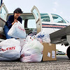 "Pilot Jan Aarsheim, of Marion, Mass., unloads bags of clothing from her six-passenger airplane at Clark County Airport on Friday afternoon. ""I can do more than write a check,"" Aarsheim said. She filled her plane with donated items and flew them down to help local residents that were affected by the March 2 tornadoes. Staff photo by Christopher Fryer"
