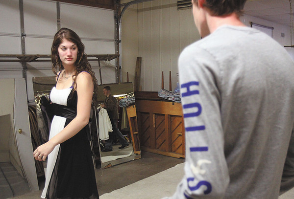 Emily Sharp tries on a dress, while her boyfriend Buddy Gaddis watches, at Prom Aid on Sunday. The fifth-annual event is hosted by the Clark County 4-H junior leaders and held at the Clark County 4-H Fairgrounds in Charlestown. Staff photo by C.E. Branham