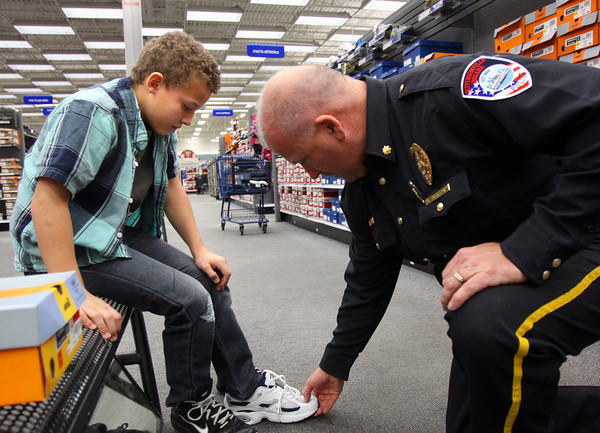 Jeffersonville police officer Glen Jackson fits Jamon Gibson in a shoe at the Meijer In Jeffersonville on Monday. The Jeffersonville FOP Lodge 100, Jeffersonville officers and families, and a $5,000 donation from Meijer gave 24 children from the community a shopping spree for clothes and toys. Staff photo by C.E. Branham
