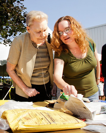 Joyce Farabee, left, of New Albany, and her daughter, Tammy Gregg, of Louisville, look through items that were removed from the 25-year-old Duke Energy time capsule that was opened during a ceremony at the company's Clarksville location on Wednesday morning. Farabee's deceased husband and Gregg's father, Robert Farabee, a retired Duke Energy employee, was present when the capsule was buried in September of 1987. Staff photo by Christopher Fryer