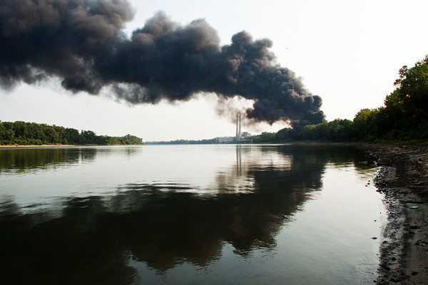 Smoke pours over the Ohio River as large bales of plastics burn at Riverside/QRS Recycling in New Albany on Saturday evening. The fire started around 5 p.m. and firefighters from 10 Southern Indiana fire departments were on the scene to help contain the blaze. Staff photo by Christopher Fryer